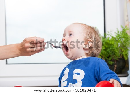 feeding baby with a spoon open mouth