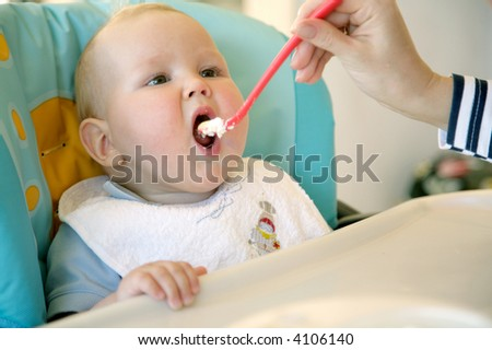 feeding cute baby boy - stock photo