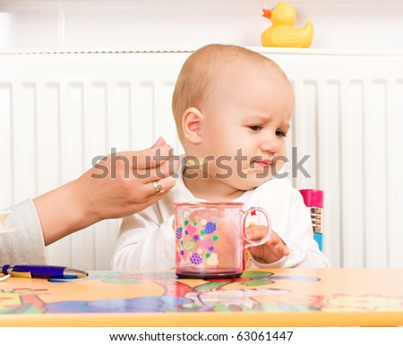 Feeding procedure of a little baby - stock photo