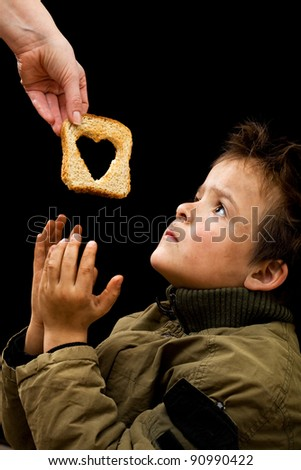 Feeding the poor concept with dirty kid receiving slice of bread - on black - stock photo