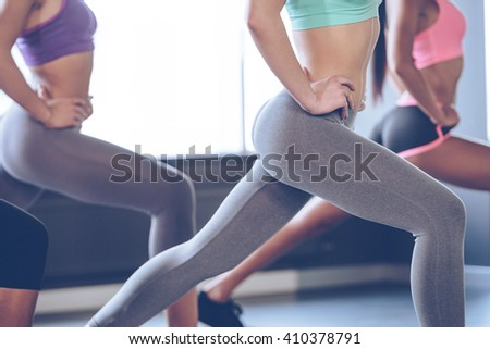 Feel burn in buttocks. Side view part of young women with perfect buttocks in sportswear exercising while standing in front of window at gym - stock photo