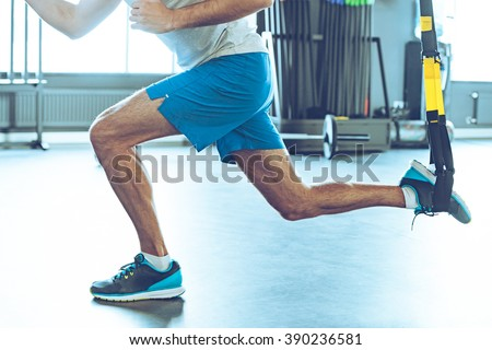 Feel strength and balance. Side view part of young man in sportswear exercising at gym - stock photo