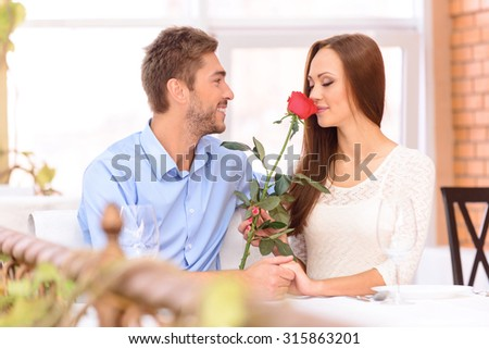 Feel the aroma. Beautiful positive woman witting in the restaurant with her love heart and holding flower while smelling it