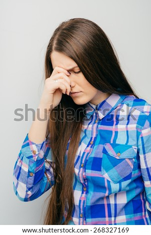 Feeling awful headache. Beautiful young women touching her head and keeping eyes closed while standing against white background - stock photo