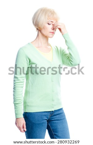 Feeling awful headache. Depressed senior woman holding head in hand and keeping eyes closed while standing isolated on white background - stock photo