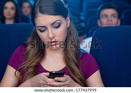 Feeling bored at the cinema. Bored young woman holding a mobile phone and looking at it while watching movie at the cinema - stock photo
