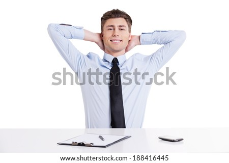 Feeling calm and confident. Handsome young man in shirt and tie sitting at the table and holding hands behind head while isolated on white   - stock photo