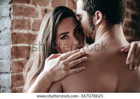 Feeling calm and protected. Close-up of beautiful young shirtless couple hugging while woman looking over shoulder of her boyfriend - stock photo
