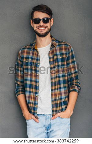 Feeling casual today. Cheerful young man in sunglasses holding hands in pockets and looking at camera with smile while standing against grey background