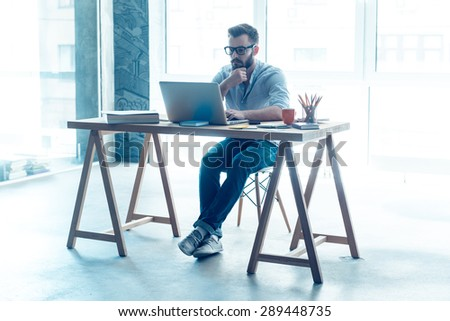 Feeling comfortable at his working place. Concentrated young beard man working on laptop while sitting at his working place in office - stock photo