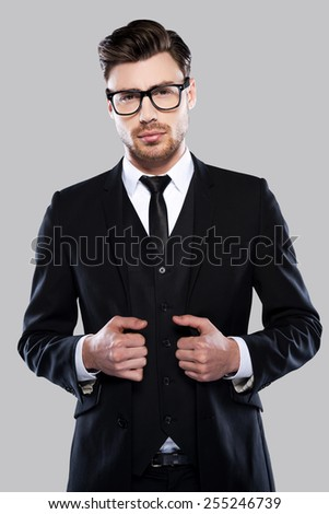 Feeling comfortable in my skin. Confident young man in formalwear and eyeglasses adjusting his jacket and looking at camera while standing against grey background - stock photo
