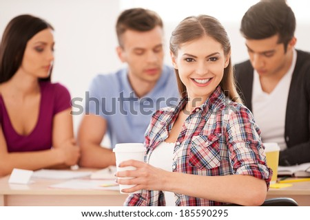 Feeling confident about her final exam. Four cheerful students sitting together at the desk and studying while beautiful woman looking over shoulder and smiling - stock photo