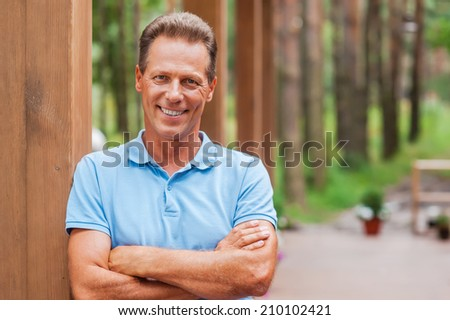 Feeling confident and relaxed. Confident mature man keeping arms crossed and smiling while standing outdoors