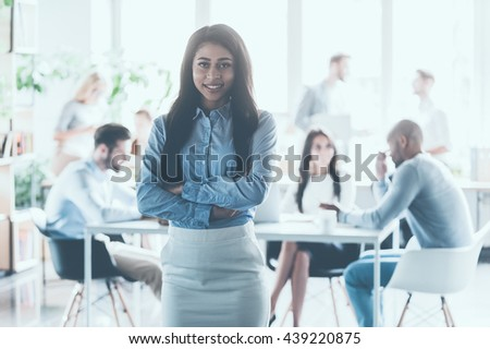 Feeling confident in her team. Beautiful young African woman keeping arms crossed and looking at camera with smile while her colleagues working in the background   - stock photo