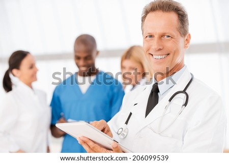 Feeling confident in his colleagues. Confident medical doctor working on digital tablet and smiling while his colleagues talking in the background - stock photo