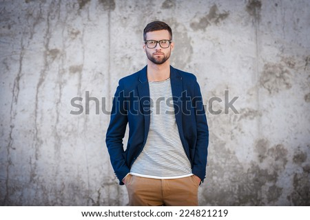 Feeling confident in my skin. Handsome young man in smart jacket holding hands in pockets while standing in front of the concrete wall - stock photo