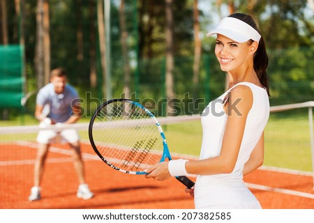 Feeling confident of winning. Beautiful young woman holding tennis racket and looking over shoulder with smile while man in sports clothing standing in the background   - stock photo