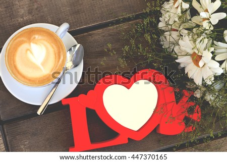 Feeling, date and love concept. Cup of hot coffee with milk and foam, red plastic frame and flower bouquet on the wooden table in the restaurant or cafeteria. - stock photo