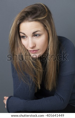 feeling depressed - sad young woman leaning on her hands sitting, expressing loneliness, emptiness and boredom, grey background studio
