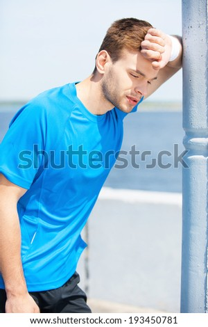 Feeling exhausted after running. Tired young man holding hand on forehead and looking away while standing outdoors