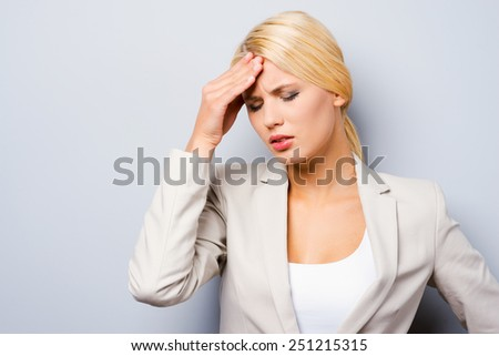 Feeling exhausted. Depressed young businesswoman touching her cheekbone and keeping eyes closed while standing against grey background - stock photo