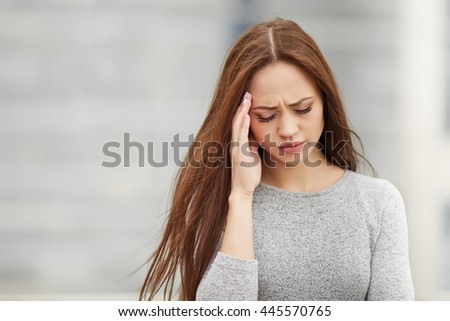 Feeling exhausted. Depressed young businesswoman touching her head and keeping eyes closed while standing against grey background. - stock photo