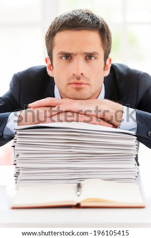 Feeling exhausted. Depressed young man in formalwear looking at camera and leaning his face at the stack of documents laying on the table  - stock photo