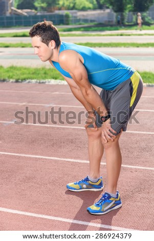 Feeling exhausted. Portrait of young attractive man standing tired after training. - stock photo
