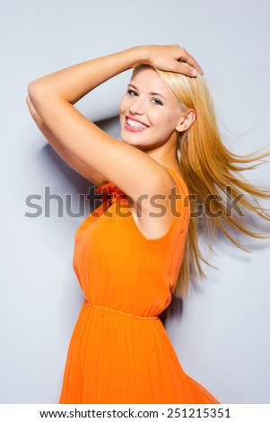 Feeling flirty. Beautiful young blond hair woman in pretty dress keeping hands in head and smiling while standing against grey background   - stock photo