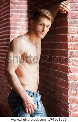 Feeling flirty. Handsome young shirtless man leaning at the brick wall and looking at camera