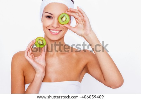 Feeling great thanks to a healthy diet. Beautiful young woman wrapped in white towel  holding piece of kiwi in front of her eye while standing against white isolated background - stock photo