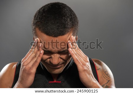 Feeling headache after workout. Closeup image of young muscular African man holding head in hands and keeping eyes closed while standing against grey background