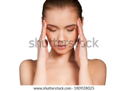 Feeling headache. Beautiful young shirtless woman holding head in hands and keeping eyes closed while isolated on white background