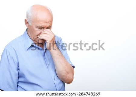 Feeling hopeless. Distempered grandfather touching his nose and keeping eyes closed while standing  isolated on white background. - stock photo