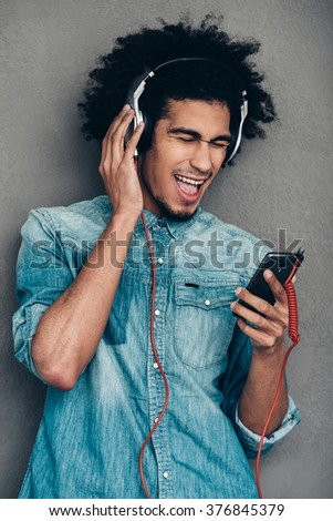 Feeling like a real star. Young African man wearing headphones and holding his smartphone while keeping eyes closed and mouth open against grey background - stock photo