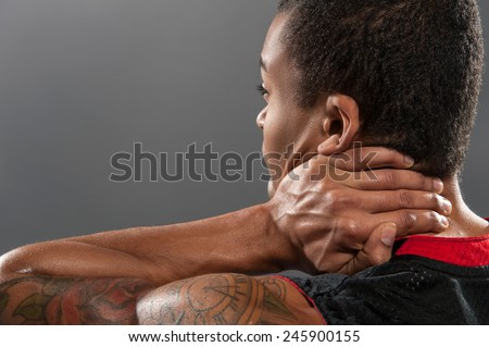 Feeling neckache after workout. Frustrated young African man touching his neck from behind and expressing negativity while standing against grey background