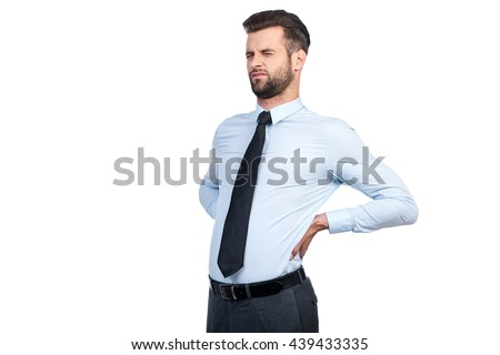 Feeling pain in his back. Frustrated young man in shirt and tie touching his back and keeping eyes closed while standing against white background  - stock photo