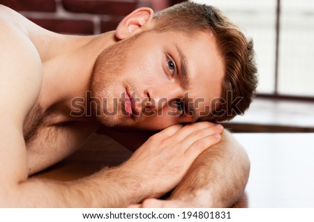 Feeling relaxed. Handsome young shirtless man looking at camera while leaning at the table  - stock photo