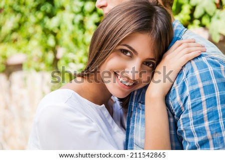 Feeling safe and peaceful. Beautiful young woman bonding to her boyfriend and smiling at camera while both standing outdoors  - stock photo