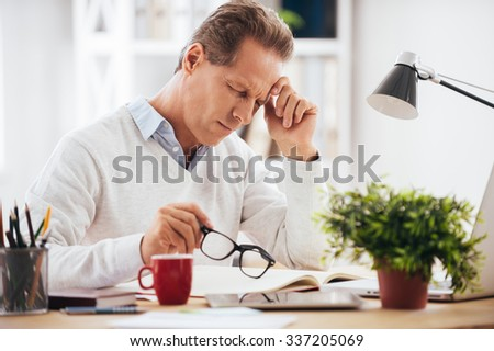 Feeling sick and tired. Frustrated mature man looking exhausted while sitting at his working place and carrying his eyeglasses in hand - stock photo