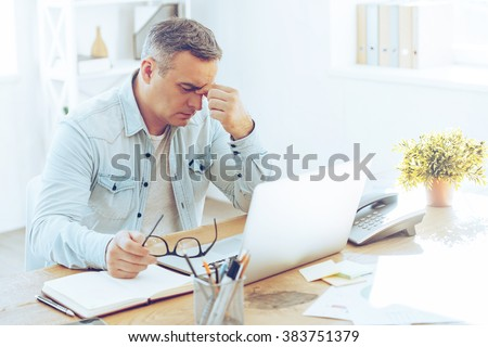 Feeling sick and tired. Frustrated mature man looking exhausted while sitting at his working place and carrying his glasses in hand - stock photo