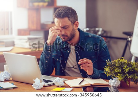 Feeling sick and tired. Frustrated young man massaging his nose and keeping eyes closed while sitting at his working place in office - stock photo