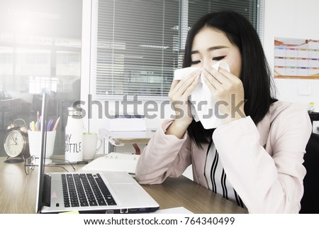 Feeling sick and tired. Sick young attractive woman with handkerchief has sneezing attack, blowing nose while sitting at her working place in office