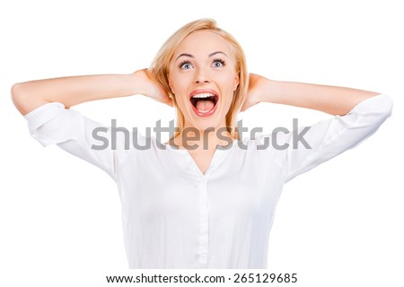 Feeling so happy! Surprised mature woman holding hands in hair and staring while standing against white background   - stock photo