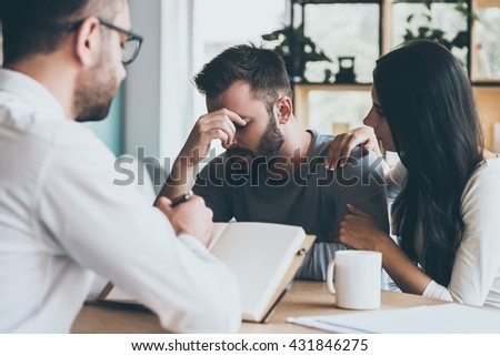 Feeling so hopeless. Young woman comforting her husband while sitting together with psychologist