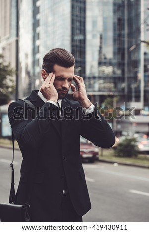 Feeling that awful headache. Frustrated young man in full suit touching his head with hands and keeping eyes closed while standing outdoors with cityscape in the background - stock photo
