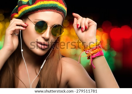 Feeling the Music. Close up Fashionable Young Woman Face, Wearing Rastafarian Hat and Trendy Round Sunglasses, Enjoying Party Music Through Headphone. Beauty Party Girl Portrait on Abstract Background - stock photo