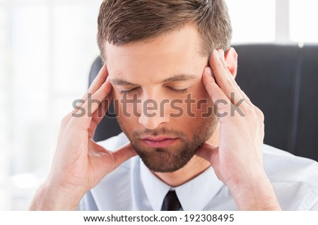 Feeling tired and depressed. Depressed young man in shirt and tie holding head in hands and keeping eyes closed while sitting at his working place - stock photo