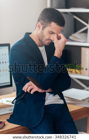 Feeling tired and depressed. Frustrated young man in smart casual wear carrying eyeglasses and keeping eyes closed while leaning at the office desk  - stock photo