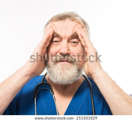 Feeling tired and stressed. Depressed mature surgeon touching his head with hands and keeping eyes closed while standing